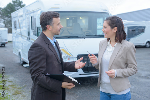 male renting agent talking with female client hiring an rv