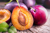 Plum. Juicy ripe organic plums closeup, over wooden background