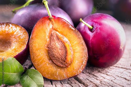 Plum. Juicy ripe organic plums closeup, over wooden background