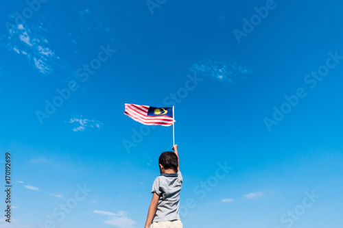Canvas Kuala Lumpur Unknown kid waving Malaysia Flag. Independence day and Merdeka Celebration. Blue sky and copy space.