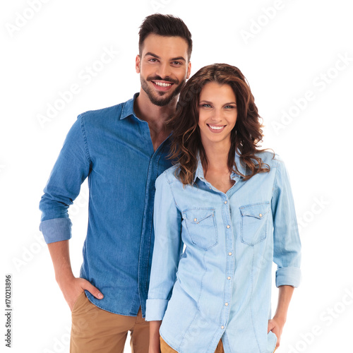 happy smiling casual couple standing with hands in pockets