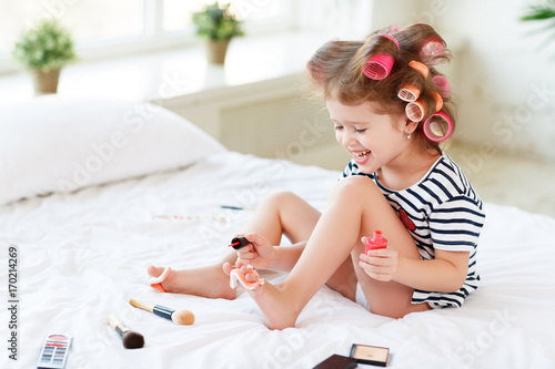 Poster Pedicure Happy funny child girl with hair curlers does a pedicure, paints nails and laughs