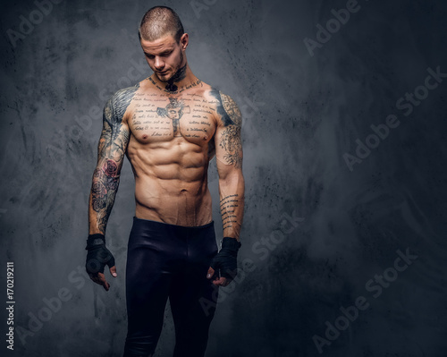 Muscular, shirtless, tattooed male over grey background.