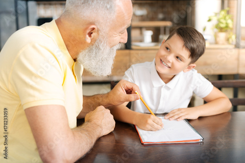 Grandfather holding grandsons pencil while helping him with homework