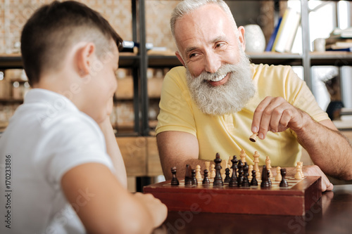 Charming senior man moving a pawn and smiling at grandson