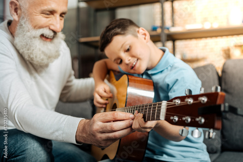 Fotobehang Muziek Smiling grandfather showing grandson how to play guitar