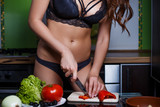 Sexy young housewife in lingerie cooking in her kitchen. Hot stylish slim lady chopping bell pepper. Fashion studio shot of woman cooking healthy food. Diet, slimness