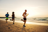 Group of sportive people running on the beach.