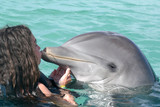 Fototapeta young girl Swimming with dolphins in the pool, kiss dolphin at dolfinarium
