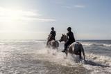 2 cavalières à vive allure dans l'eau de mer