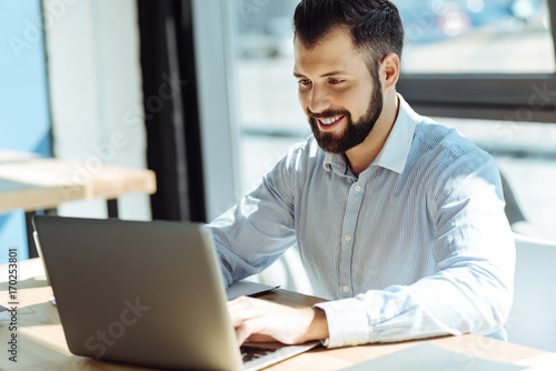 Pleasant smiling man using his laptop in office