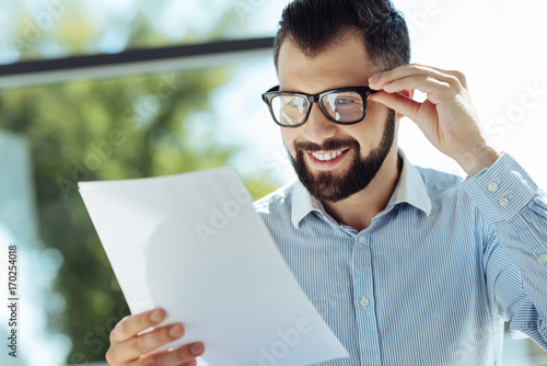 Bearded young man looking at documents and smiling