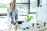 Joyful pretty woman talking on the landline phone in office
