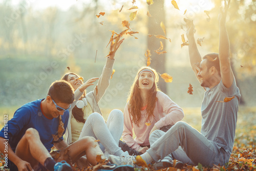 Group of friends relaxing the park on beautiful autumn day. Sitting on ground and throws leaves in the air.