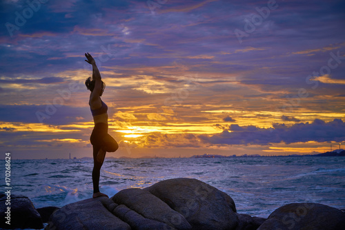 Poster Silhouette of Asian women who practice yoga on the beach at sunset, the sky is beautiful.