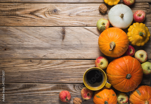 Cup of coffee and some pumpkins on wood background