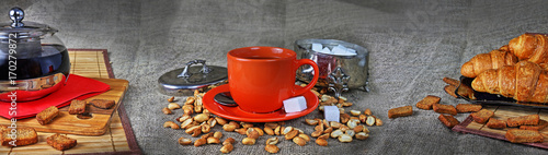 Still life panorama with a cup of tea, a teapot, croissants and a sugar bowl