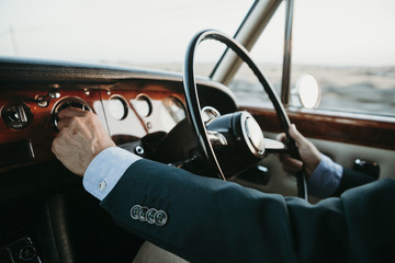 inside view of classic luxury car being driven by man.