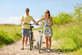 happy couple with bicycles on country road - 170297252