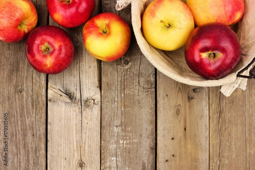 Freshly harvested apples with basket, top border on rustic aged wood background