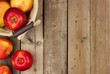 Freshly harvested apples with basket, side border on a rustic aged wood background
