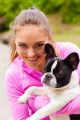 Smiling woman holding french bulldog outside