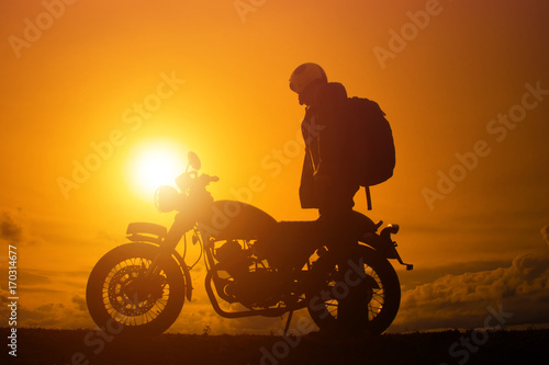 Poster Silhouette of biker man  with his motorbike,he shoulder backpack