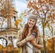 smiling young elegant woman near Eiffel tower with cellphone