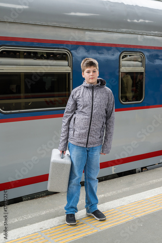 Boy teen with a travel bag near train
