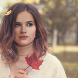 Beautiful Young Woman Fashion Model with Red Fall Mapple Leaf Outdoors, Autumn Beauty