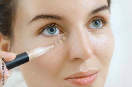 Leinwanddruck Bild Woman using concealer