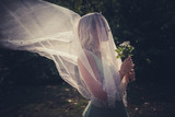 portrait of bride with veil and bouquet of wild flowers outdoor shot - 170328449