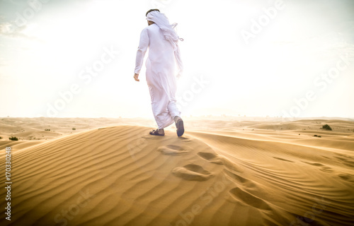Arabic man with traditional emirates clothes walking in the desert Poster