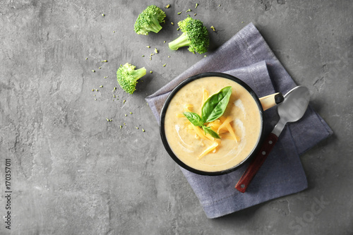 Cup with broccoli cheddar soup on kitchen table - 170357011