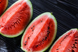 Background of fresh ripe watermelon slices on black wooden table. Top view.