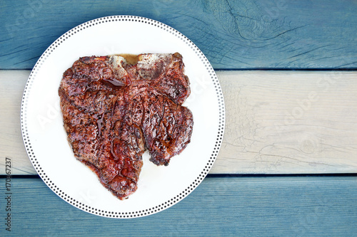 Foto op Plexiglas Steakhouse Juicy Delicious thick grilled T-bone beef steak viewed from above. Flag of Argentina background
