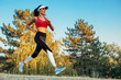 Young sports woman jogging through nature