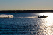 A boat and water skier silhouetted against a blue lake