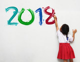 Fototapety little girl holding a paint brush painting happy new year 2018 on a white wall background