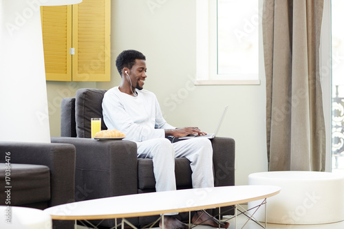 Handsome African American man enjoying lazy weekend at home: he sitting on cozy armchair and playing computer game, interior of modern living room on background