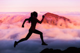 Trail runner nature landscape running woman silhouette on mountains background in cold weather with pink clouds at sunset. Amazing scenic view of peaks in altitude.