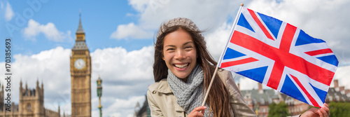Papiers peints Londres London travel tourist woman with Great Britain flag banner showing Union Jack Icon. UK European holiday destination Asian chinese girl holding United Kingdom British flag. Panorama crop.