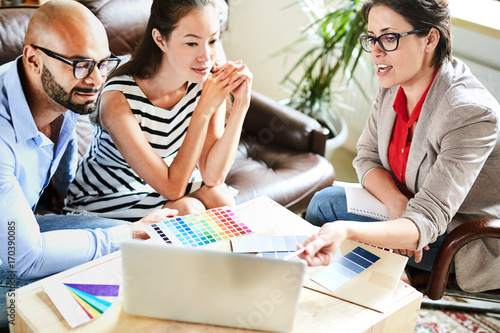 Pretty middle-aged interior designer sharing ideas with her clients while having meeting in cozy boardroom, they listening to her with interest