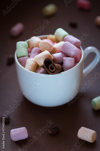 Papiers peints Chocolat Hot chocolate in a white Cup with colored marshmallows on a dark background. Selective focus.