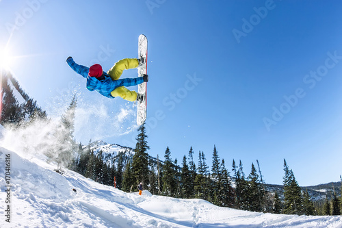 fototapeta na ścianę Snowboarder freerider jumping from a snow ramp in the sun on a background of forest and mountains