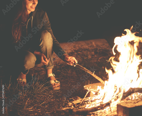 Young woman in geans and hoodie in the mountains. Young woman with fire on mountain at sunset. Girl standing near a fireplace