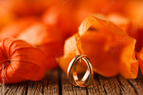 Wedding decoration. Red leaves on weathered table with wedding rings - 170419410