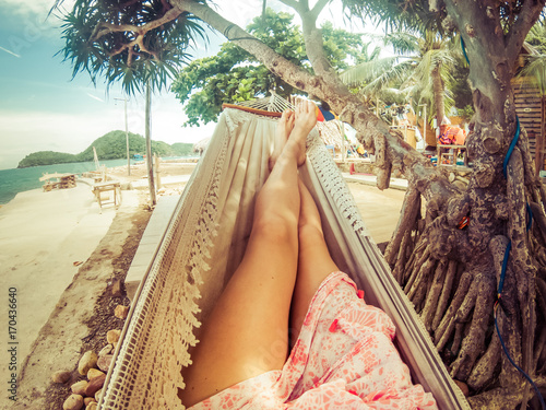 Papiers peints Tropical plage legs of woman relaxing in hammock on a tropical beach
