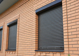Brick House Windows with rolling shutter for house protection. - 170437067