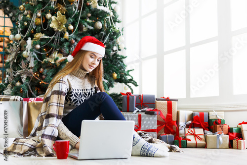 Young woman online on laptop at christmas interior